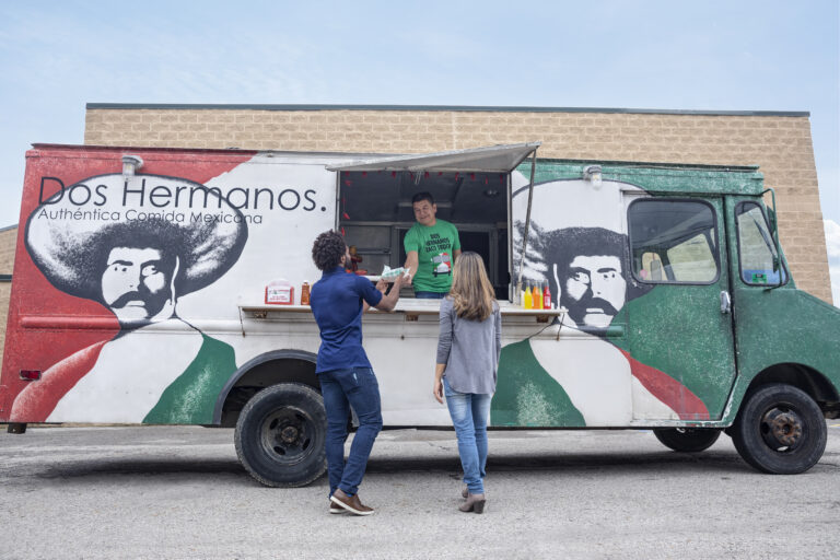 Dos Hermanos Taco Truck employee and two customers