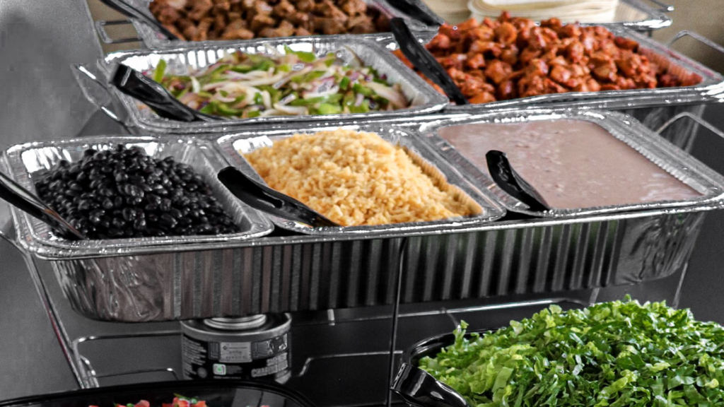 Rice, chicken, and assortment of ingredients for catering event spread